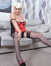 Naughty British housewife playing on the couch with a banana