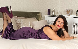 British MILF playing near herself in the matter of bed