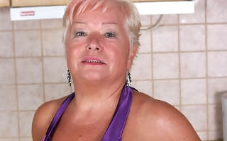 Blonde mature floozy doing herself in the kitchen