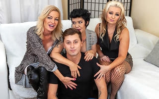 Three cougars seduce a young guy not susceptible the couch for steamy groupsex